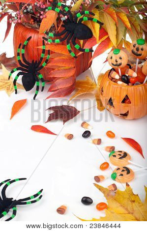 Halloween candy scattered around fall beries leaves and spiders. poster