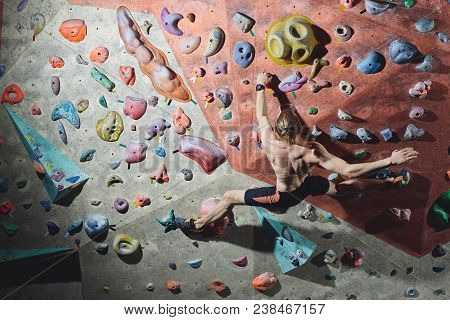 Workout Exercise. Back View Of A Man Climber Climbs Indoors In Bouldering Gym. Athletic Man Climbing