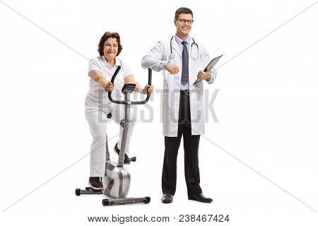 Mature woman on a stationary bike with a doctor leaning on it isolated on white background