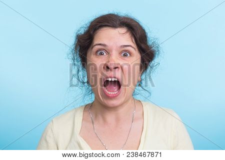 Angry aggressive woman with ferocious expression on blue background. poster