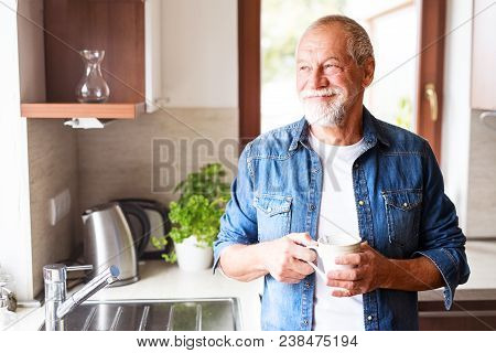 Happy Senior Man In The Kitchen. An Old Man Inside The House, Holding A Cup Of Coffee.