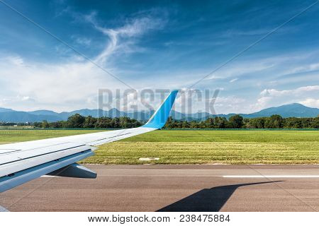 Wing Of Plane In Bergamo Airport. Airplane Is On Runway. The Plane Takes Off Or Landing. Arrival Or