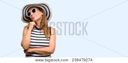 Middle age cool woman wearing summer hat and sunglasses thinking and looking up expressing doubt and wonder isolated blue background