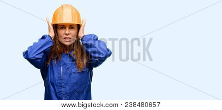 Engineer construction worker woman covering ears ignoring annoying loud noise, plugs ears to avoid hearing sound. Noisy music is a problem. isolated blue background