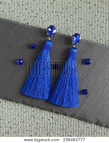 Blue Beautiful Handmade Earrings With Shiny Crystals And Tassels, Lying Flat On The Grey Stone Backg