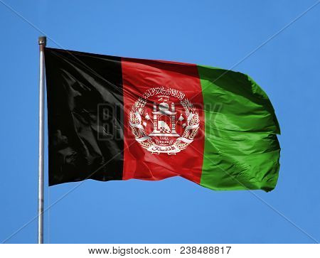 National Flag Of Afghanistan On A Flagpole In Front Of Blue Sky.
