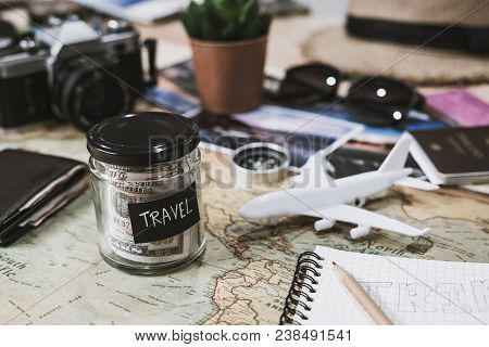 Vacation Money Saving In A Glass With Camera On Map, Travel Budget Concept