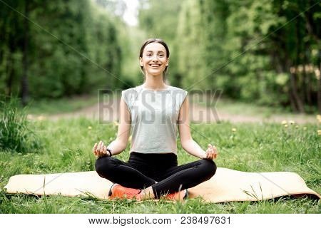 Young Woman Meditating During The Yoga Exrecise In The Park
