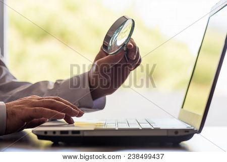 Searching On Internet Concept, Business Metaphore With Man Holding Magnifying Glass Over Computer