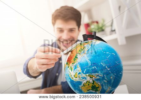Young Cheerful Man Dreaming About Air Travel Around World, Looking At Globe At Home. Handsome Guy Pl