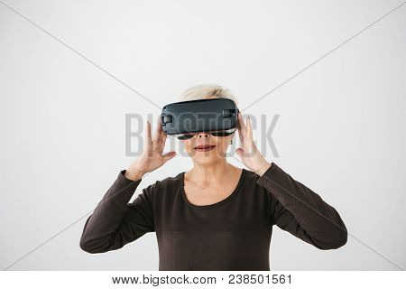 An Elderly Woman In Virtual Reality Glasses. An Elderly Person Using Modern Technology