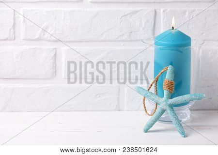 Blue Burning Candle And Sea Star  Near By White Brick Wall. Selective Focus. Place For Text.
