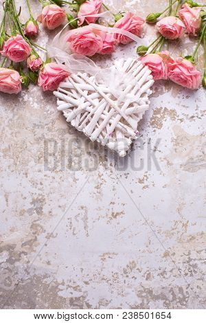 Frame From  Pink Roses Flowers And Decorative Heart On Grey Vintage Textured Background. Floral Stil
