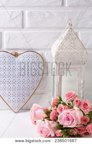 Fresh  Pink Roses Flowers, Heart  And Decorative Lantern Against  White Brick Wall. Floral Still Lif