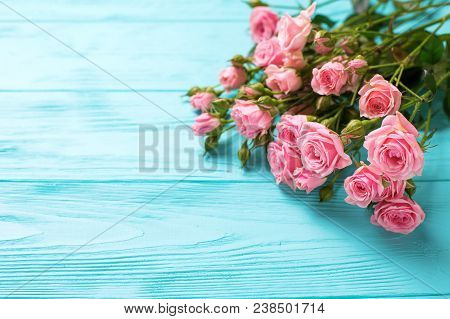 Border From Tender Pink Roses Flowers On Turquoise Wooden Background. Floral Still Life.  Selective