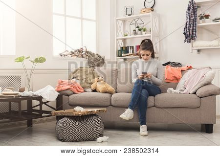 Desperate helpless woman sitting on sofa in messy living room. and chatting on mobile, surrounded by many stack of clothes. Disorder and mess at home, copy space poster
