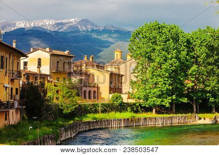 Rieti, City Of Central Italy. Fiume Velino With Ancient Houses And The Terminillo Mountain At The To