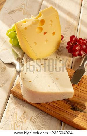 Dutch Hard Cheese Maasdam Or Emmentaler, Cheese With Holes And White Hard Goat Cheese With Coriander