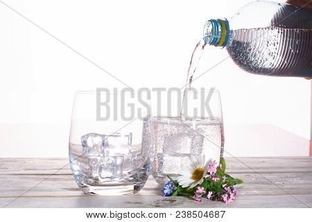 Pouring Of Sparkling Soda Mineral Drink Water In Glasses With Ice Cubes Close Up Copy Space