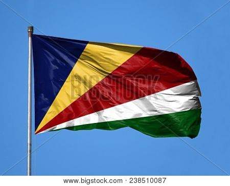 National Flag Of Seychelles On A Flagpole In Front Of Blue Sky.