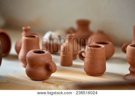 Ceramic Dishware On Worktop And Shelves With Its Lids In Pottery Workshop, Selective Focus, Close-up