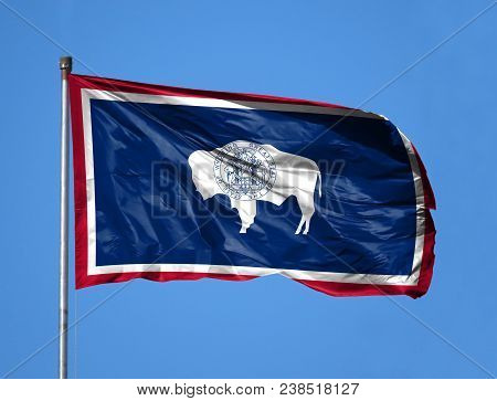 National Flag State Of Wyoming On A Flagpole In Front Of Blue Sky.