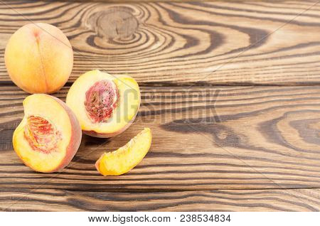 One Whole Peach And Two Half Of Fresh Ripe Peach With Peach Stone And One Slice Of Peach On Rustic O