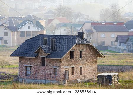 Brand New Spacious Brick Two Story Residential House With Tiling Roof And Windows Openings In Suburb