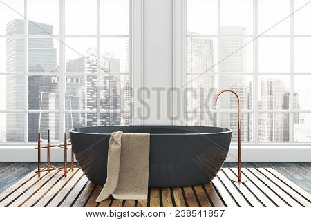 Luxury Bathroom Interior With A Dark Wooden Floor, White Walls, And A Black Bathtub. A Beautiful Cit