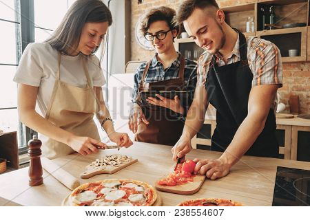 People Cooking Together. Company Of Friends Chopping Ingredients On Cutting Boards And Read Recipe O