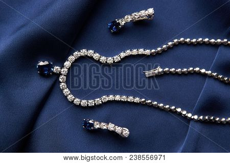 Close-up of women's platinum necklace and earrings with a diamond and blue precious sapphire stone . Luxury female jewelry poster