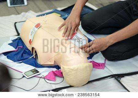 First aid cardiopulmonary resuscitation course using AED training. selective focus placing electrode poster