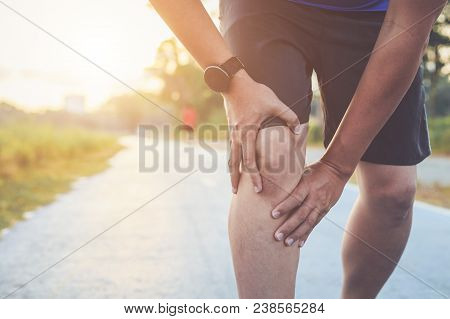 Injury From Workout Concept : The Asian Man Use Hands Hold On His Knee While Running On Road In The