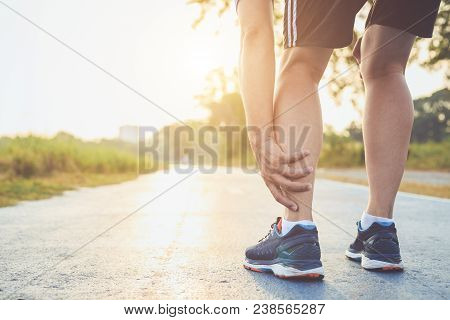 Injury From Workout Concept : The Asian Man Use Hands Hold On His Ankle While Running On Road In The