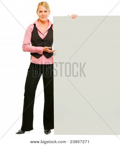 Full Length Portrait Of Smiling Business Woman Pointing On Blank Board