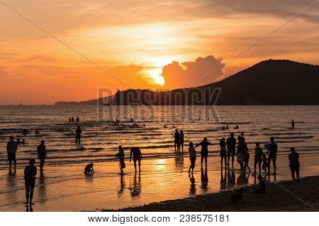 Sattahip, Chonburi, Thailand - April 21, 2018: Silhouetted Scene Of Golden Sunset Sky At Crowded Bea