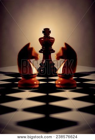 Black king with light behind, two white knights mirrored for symmetry, on diagonal chess board. Concepts business or religious or board meeting. Focus on King. poster