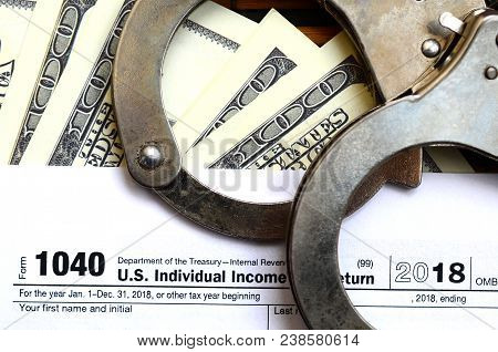 Police Handcuffs Lie On The Tax Form 1040. The Concept Of Problems With The Law In The Aftermath Of