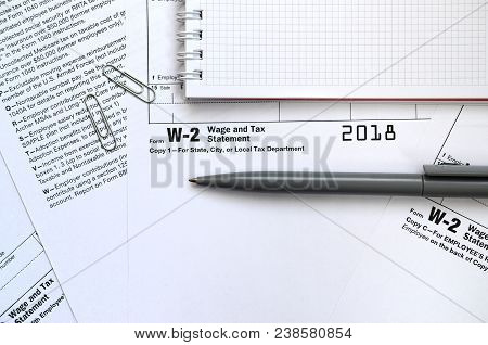 The Pen And Notebook On The Tax Form W-2 Wage And Tax Statement. The Time To Pay Taxes
