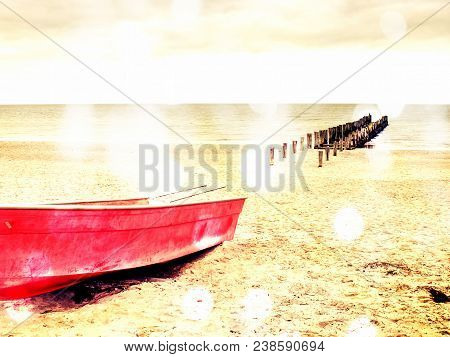 Abstract Effect.  Abandoned Red Paddle Boat On Sandy Beach Of Sea.  Smooth Water Level Within Mornin