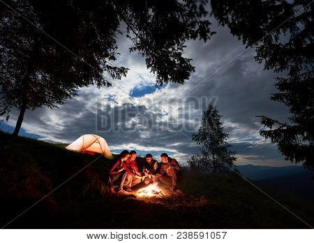 Night Camping In The Mountains. Group Of Friends Hikers Having A Rest Around Campfire With Beer, Enj
