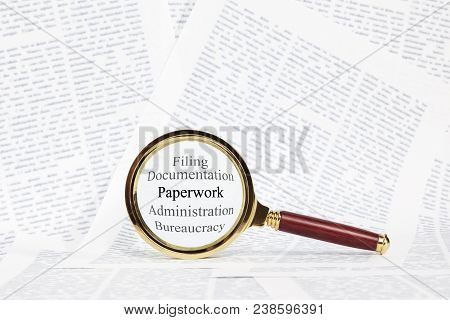 Paperwork And Magnifying Glass Concept - A Magnifying Glass Over The Words Paperwork, Administration