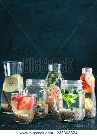 Different Chia Water In Glass On Dark Background. Chia Infused Detox Water With Berries, Fruits And