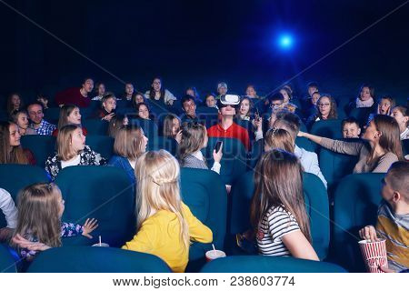 View Of Audience Watching Film In Movie Theatre. Boy In Virtual Glasses Sitting In Centre. Curious
