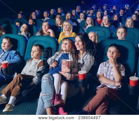 Children, Teens, Adults Watching Film With Steadfast Eyes In Modern Movie Theatre. Smiling Viewers E
