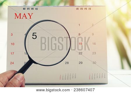 Magnifying Glass In Hand On Calendar You Can Look Day Five Of Month,focus Number Five In May,concept