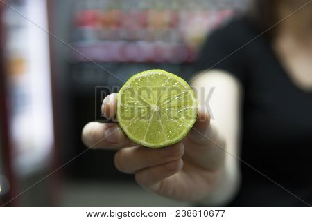 Hand Holding Half Of Green Lime. Halves Of Lime In Hand Over The Bar On Background. Creative And Sty