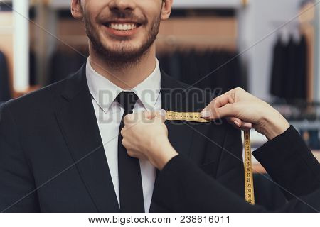 Close Up. Tailor Uses Measuring Tape To Measure Dimensions Of Customer For Tailoring Suit. Suit Meas