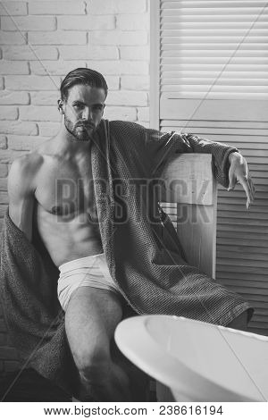 Sexy macho with six pack, ab, torso in bathroom, fitness. Man with fit body in underwear, bathrobe, fashion. Health, bodycare, hygiene. Fitness, bodycare, wellness. Fashion, home wear, underwear. poster