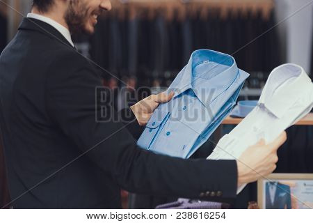 Successful Young Businessman In Suit Chooses Shirts To Buy. Boutique Of Business Suits. New Suit Pur